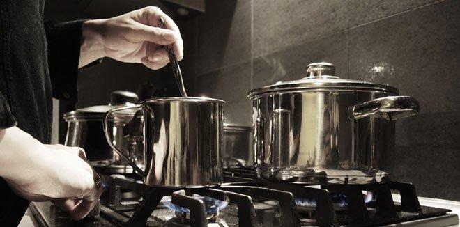 Koch mit Kochtöpfen in der Küche beim kochen