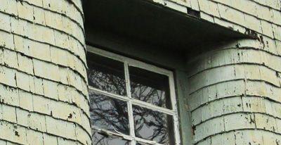 Foto eines sanierungsbedürftigen Haus/ Fenster