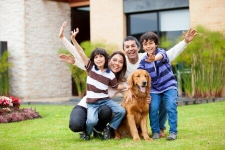 Zufriedene Familie vor Haus