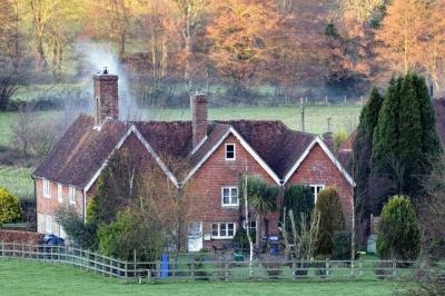 Alter Schornstein qualmt aus einem unsaniertem Haus