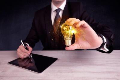 Energieberater hält Glühbirne während er am Tablet arbeitet
