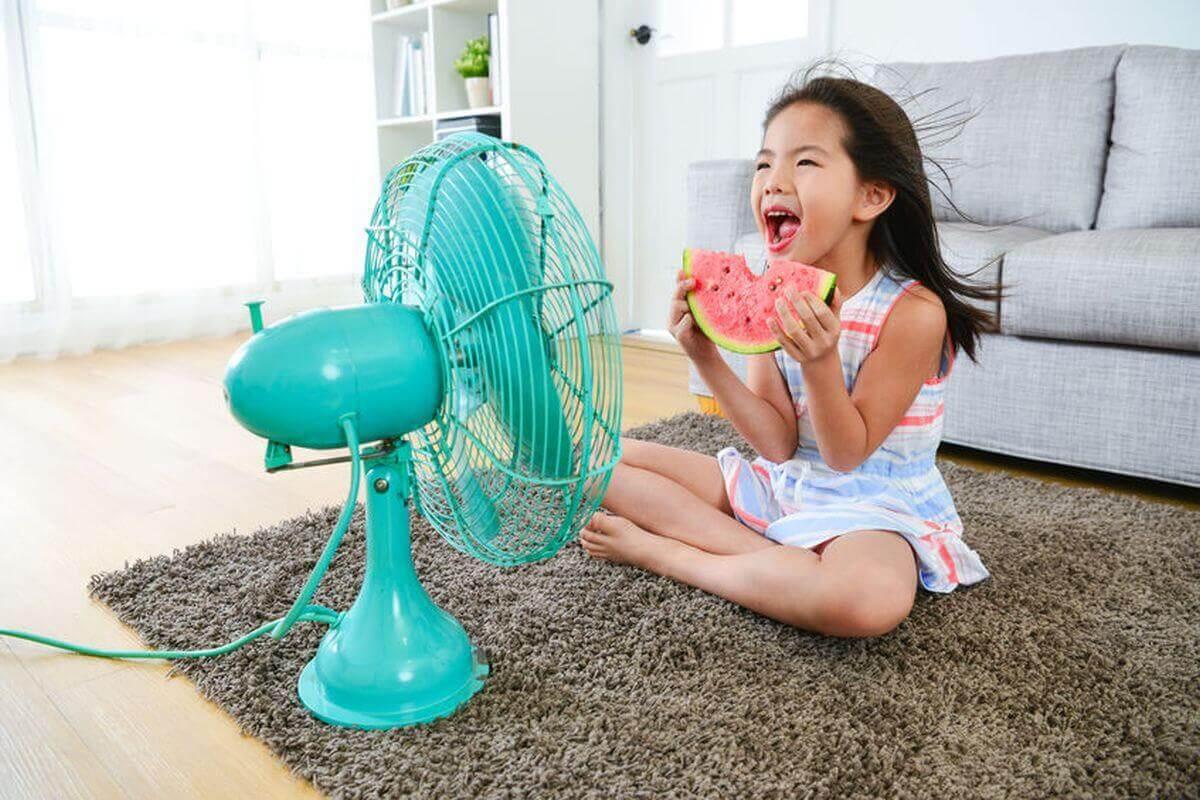 Kleines Mädchen kühlt sich vor vor Ventilator