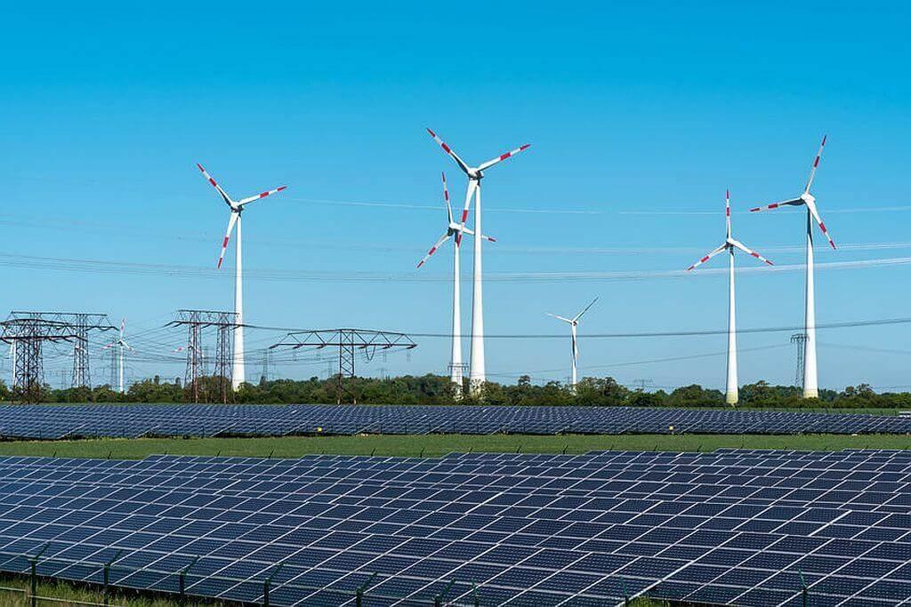 Solaranlage und Windräder in der Nähe einer Stromleitung