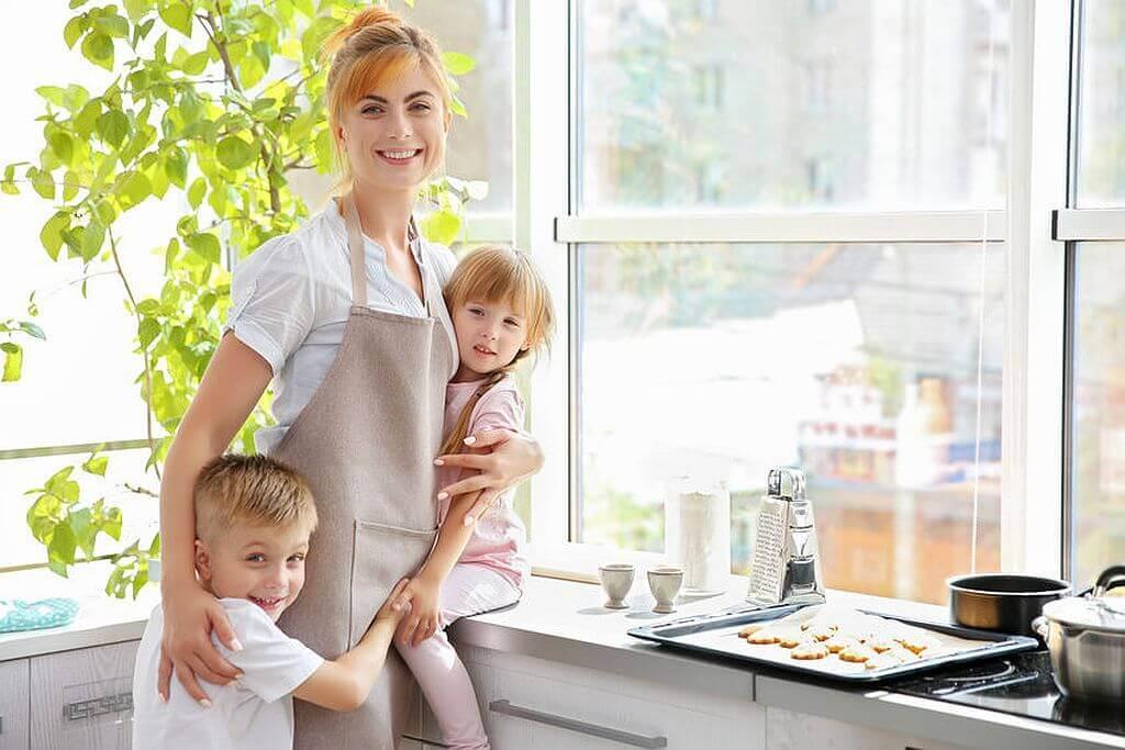 Junge Frau mit Kindern in der Küche